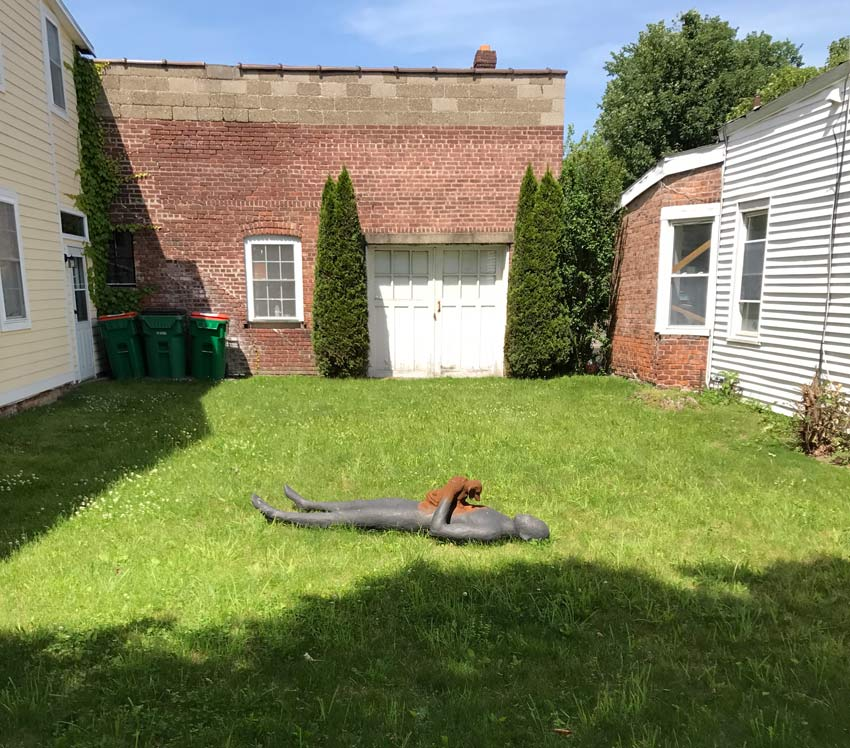 sculpture of man laying in grass with puppy on chest, in Beacon NY