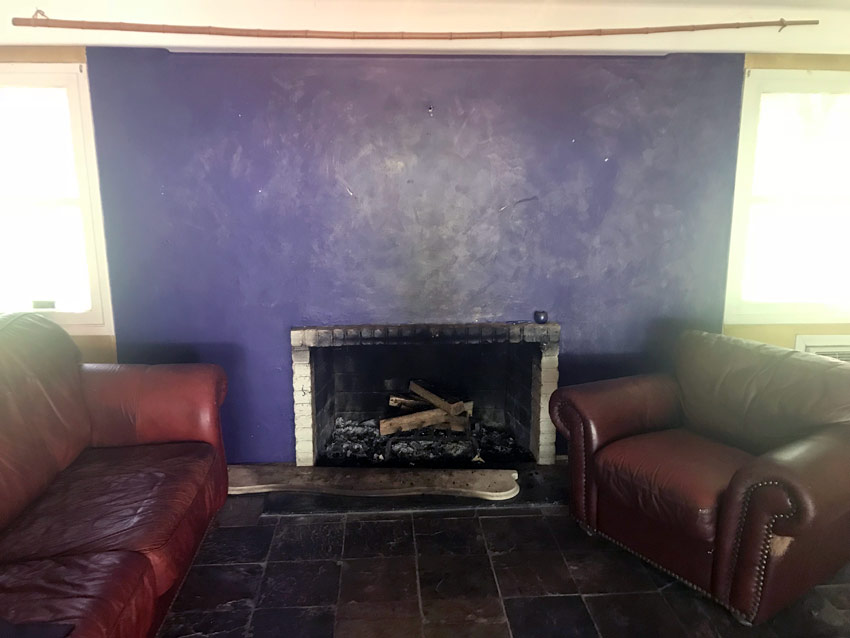 fireplace with soot stains on blue wall in a home for sale